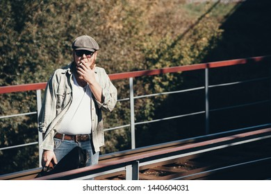 Bluesman with guitar case smokes cigarette on railroad. Blues musician with cigarette on railway. Cool guy with guitar. Bearded man travels light. Wandering hippie lifestyle. Eccentric smoker inhales.