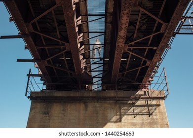 Bluesman with guitar case walks on railroad bridge. Silhouette of blues musician on rusty railway bridge. Cool guy with guitar. Bearded man travels light. Wandering hippie lifestyle. Eccentric man.