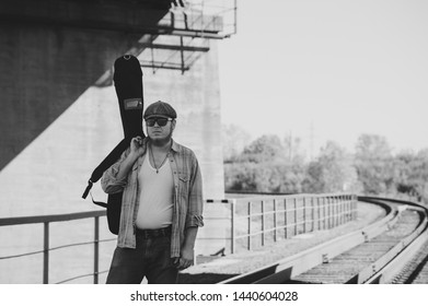 Bluesman with guitar case walks on railroad. Blues musician on railway in grayscale. Cool guy with guitar. Bearded man travels light. Wandering hippie lifestyle. Eccentric man in monochrome.