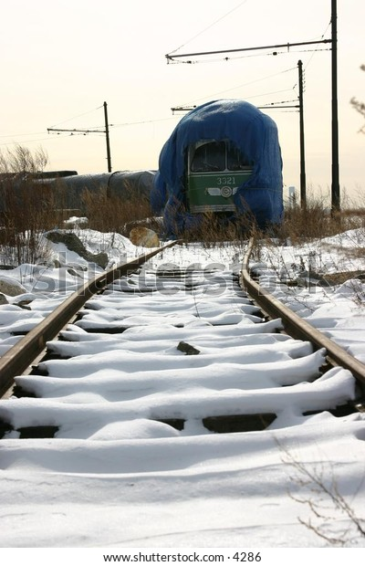 blue-tarped train on snowy tracks