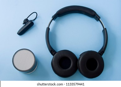 Bluetooth headset, speaker and earphone isolated on pastel blue desk. Flat lay.