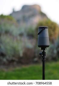 Bluetooth speaker on tripod in garden.