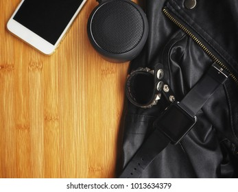 Bluetooth speaker with smart phone and smartwatch with leather jacket on work table