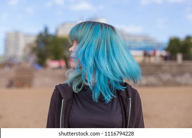 Blue-turquoise hair in flight, shake your head. Colored staining, hairstyle. Modern young woman, student, informal.