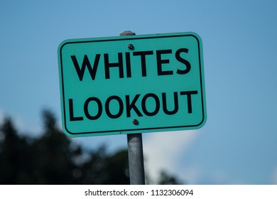"""A blue/turquoise sign with black text that reads """"Whites Lookout""""."""