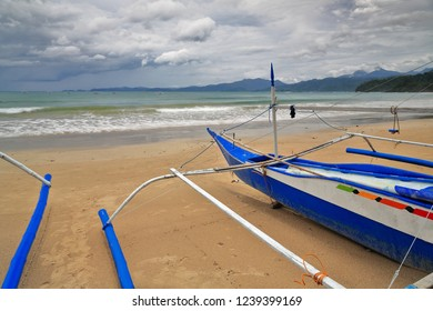 Blue-white painted fishing bangka motor boat with bended bamboo booms and double outrigger stranded on the sandy beach of Sabang town. Puerto Princiesa Subterranean River Nnal.Park-Palawan-Philippines