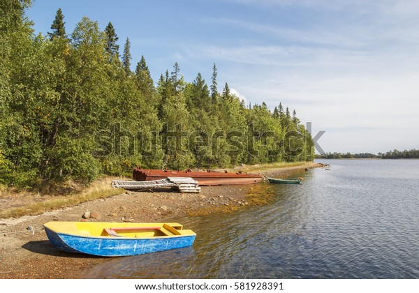 Blue-yellow boat moored to the sea coast on the island of Solovki