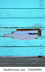 Bluish green painted fence of wood boards, with a hole through which you can see the surface of an ocean and a vessel sailing by