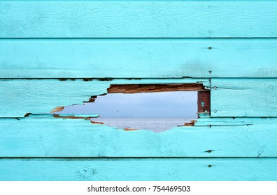 Bluish green painted fence of wood boards, with a hole through which you can see the surface of an ocean