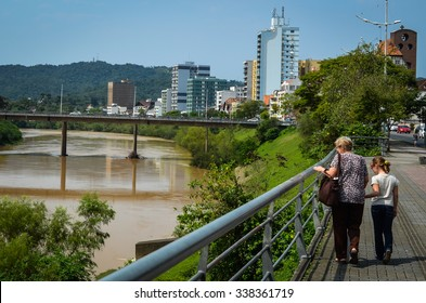 BLUMENAU, SANTA CATARINA/BRAZIL - SEPTEMBER 19 2015: Grandma and Grand daugther walking and looking at Itajai river, Blumenau, Santa Catarina/Brazil.