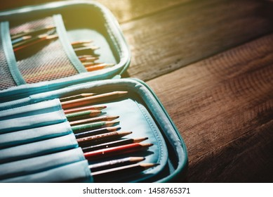 blunt coloured pencil in a pencil case on a wooden desk in a bleak light. concept of a education, childhood and creativity
