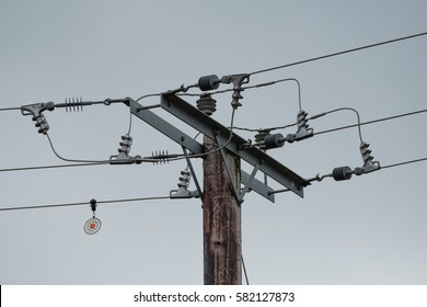 BLUNTISHAM, CAMBRIDGESHIRE, UK - CIRCA FEBRUARY 2017: High voltage electricity cables seen with there ceramic insulators atop wooden poles in which the power feeds a rural village.