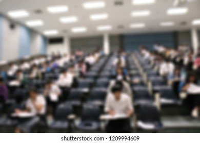 Blur abstract background of examination room with undergraduate students inside. Blurred view of student doing final test in exam hall.