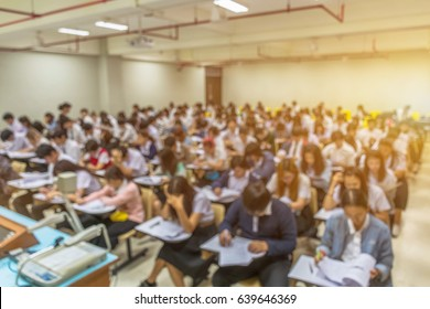 Blur abstract background of examination room with undergraduate students inside. Blurred view of student doing final test in exam hall. Blurry view of study chairs in classroom of university or campus
