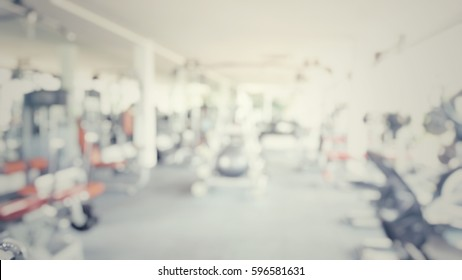Blur abstract background of exercise equipments in in modern fitness gym. Blurry people work out in workout room.Defocus Fitness center with traineger equipments in vintage retro tone.
