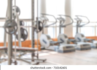 Blur abstract background of exercise equipments in in modern fitness gym. Blurry treadmill in workout room.Defocus Fitness center with traineger equipments .