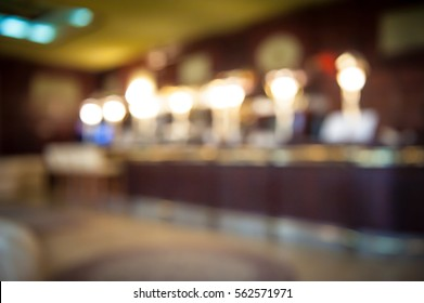 Blur abstract background interior of dark brown bar. Empty glasses for wine above a bar rack. Classic bar counter with bottles in blurred background. Interior of pub or bar at night. Luxury restaurant