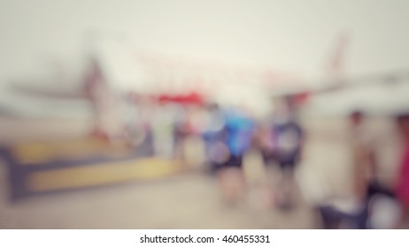 Blur abstract background passengers in queue line travelling with carry baggage. Blurry view outside terminal boarding airplane, people climbing ramp to the plane. Defocus people walking to aircraft.