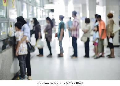 Blur abstract background perspective view of waiting zone seat row in hospital building interior. Blurry patients waiting to see doctors, people paying money at cashier counter and wait for pharmacy.