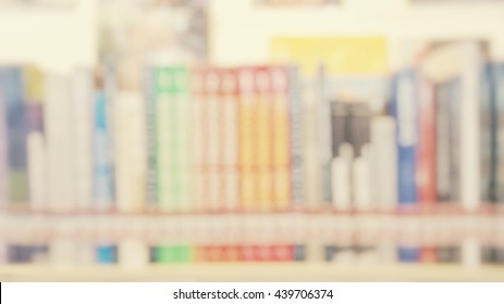 Blur abstract background of shelf of books in public library. Blurry view of literature in bookshelves for reading in university  in vintage style.