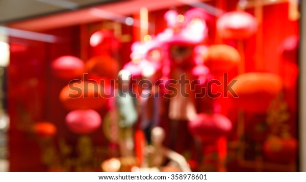 Blur abstract motion of a fashion boutique/outlet windows display with mannequin and Chinese New Year red lantern decoration in an Asian shopping mall. Panoramic style