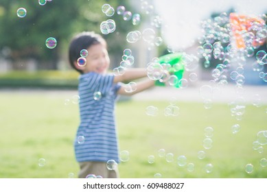 Blur of Asian child Shooting Bubbles from Bubble Gun in the park