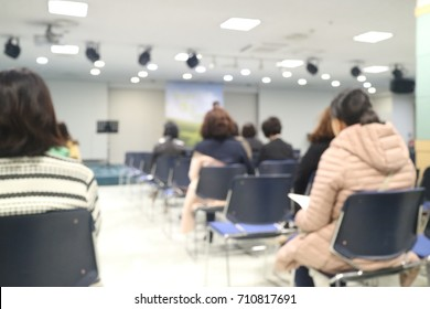 Blur audience sitting in auditorium or hall or classroom
