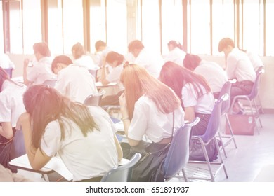 Blur back view abstract background of examination room with undergraduate students inside. university student in uniform sitting on row chair doing final exam in classroom.
