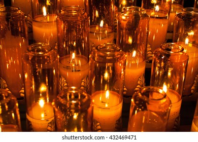 blur background of burning candles in orange transparent chandeliers in a church setting