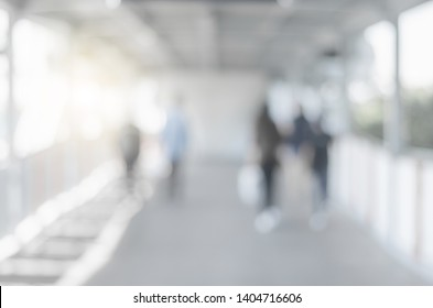 blur background image of empty modern sky walk way in city with people walking indoor and sunlight abstract gray blur bokeh.