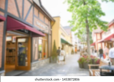 Blur background outdoor outlet shopping center in summer season with building,tree,green leaves and shop. Concept shopping summer big sale and black Friday.
