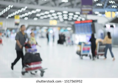 Blur background of passengers pushing trolley with baggage within international terminal at airport. Timetable departure and arrival board showing digital time. Tourist check-in at airline counter.