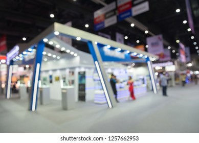 Blur background of people in electronic fair expo at big exhibition hall event trade show room. Meetings, incentives, conferences and exhibitions (MICE) business and commercial trading concept.