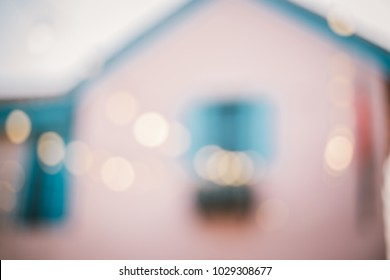 Blur background. Pink house and golden bokeh in evening.