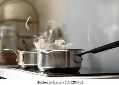 Blur background. Selective focus. Boiling water with a steam in a pot on a electric stove in the kitchen