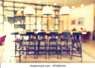 Blur background view empty working table and high chair for co-working space or group meeting discussion in coffee shop