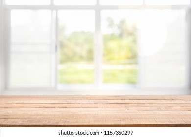 Blur background of white window glass and green view from garden with epty of wood table. Using for Mock up template for craft display of your design,Banner for advertise of product.