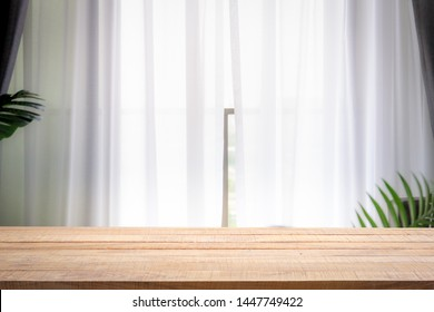 Blur background of white window glass with empty of wood table. Using for Mock up template for craft display of your design.