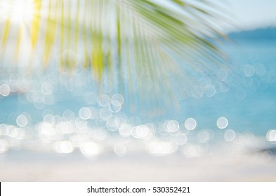 Blur beautiful nature green palm leaf on tropical beach with bokeh sun light wave abstract background. Copy space of summer vacation and business travel concept. Vintage tone filter color style.