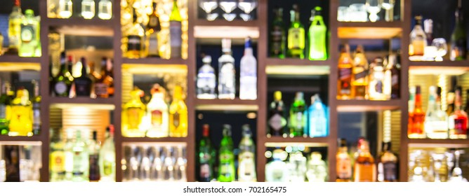 Blur bottles of spirits and liquor on bar counter