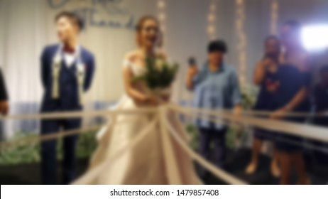 Blur of Bride is holding flower bouquet with white pearl color ribbon for bridesmaid, who is lucky to get beautiful floral bouquet that is meant to bring good luck to women at Wedding reception.