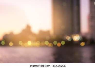 Blur building at riverside background with bokeh lights sunset time