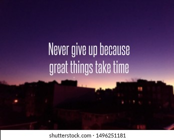 """Blur buildings view on background with an inspirational quote """" Never give up because great things take time"""""""