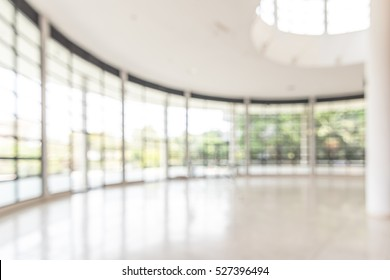 Blur business office background empty white room lobby hall interior with glass wall window and blurry light bokeh