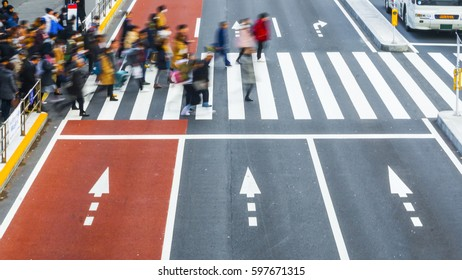 Blur business people walk fast across the pedestrian crosswalk in the city road with the signage on arrow on the grey and red concrete road. (on top aerial view)