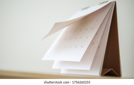 Blur Calendar page flipping sheet on wood table background business schedule planning appointment meeting concept