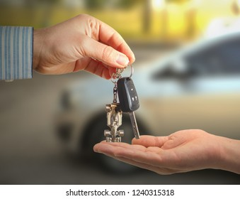 blur car in the background and person holding car key in hands