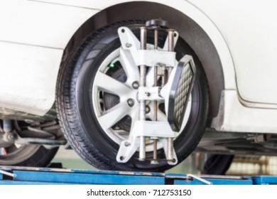 Blur - car wheel centering machine adjustment selective focus on machine caliper