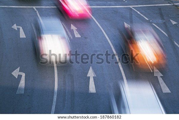 Blur cars in rush hour on white markings and arrows.