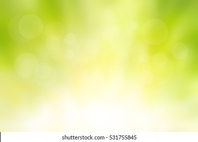 Blur circle bokeh green leaf background. Yellow leaves rays light flare nature backdrop. Abstract blurred scene for web advertising. Soft focus foliage during summer with sunbeam wallpaper.